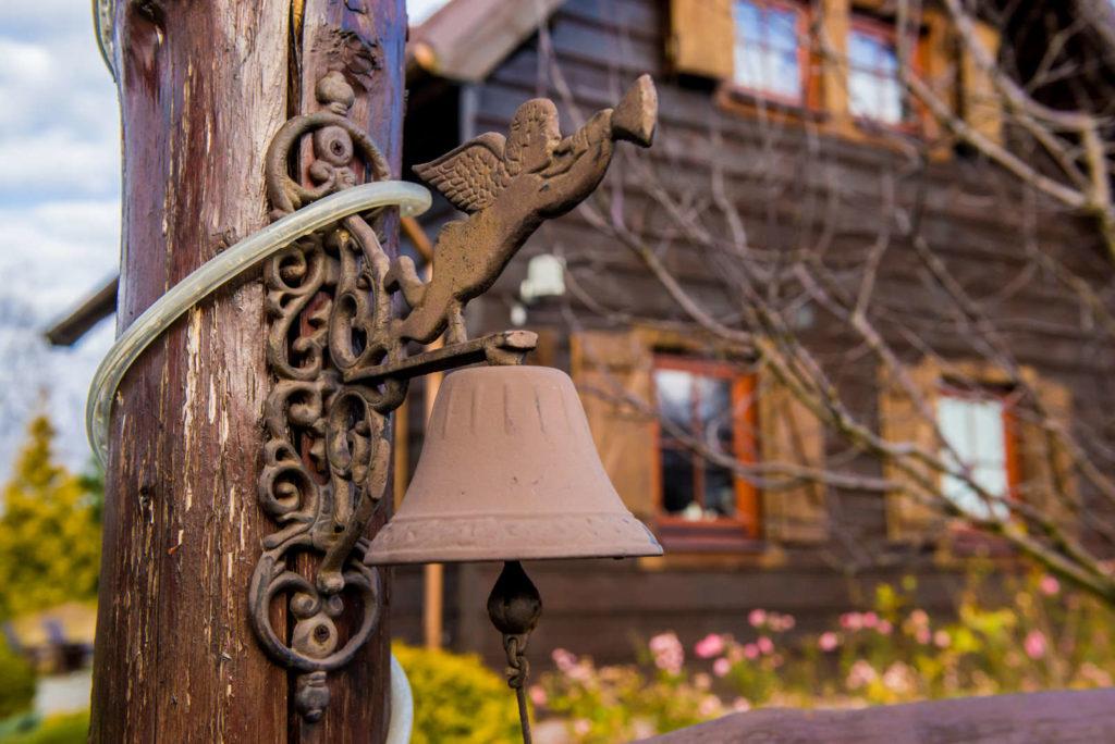 dzwonek przed drewnianą zagrodą